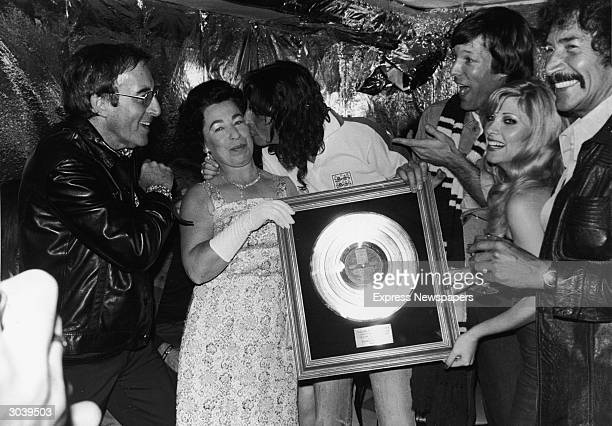 American rock singer Alice Cooper kisses Queen Elizabeth II impersonator Jeanette Charles while holding his gold record plaque as LR actors Peter...