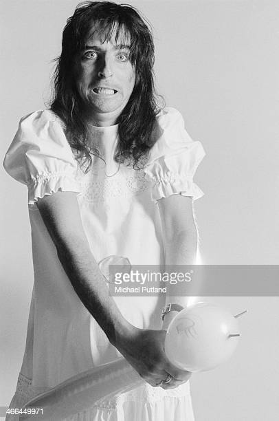 American rock singer Alice Cooper wearing a dress and throttling a balloon London March 1974