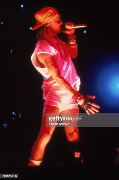 American rock singer Axl Rose of the band Guns N' Roses performs on stage dressed in a white tank top and bike shorts a backwards baseball cap and a...