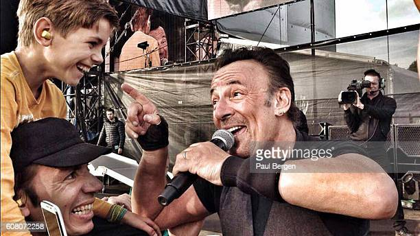 American rock singer Bruce Springsteen sings to a young boy in the crowd held up on shoulders at Malieveld The Hague Netherlands 14th June 2016