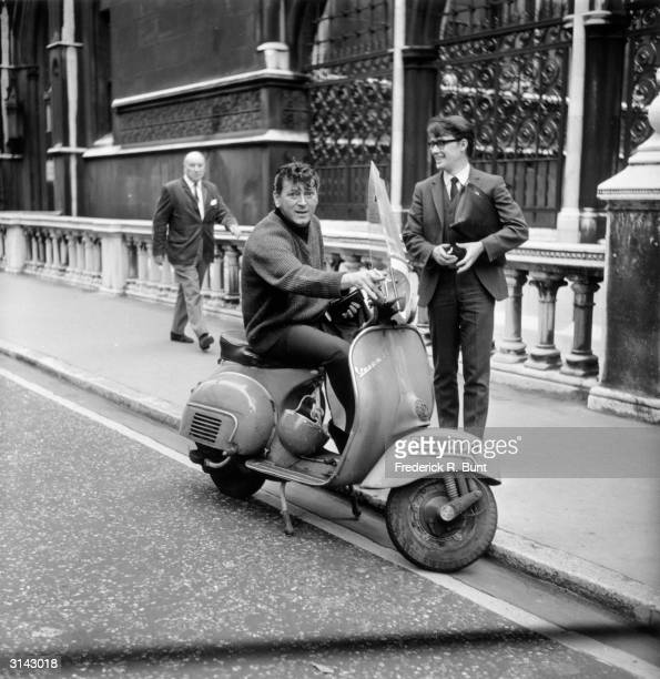 American rock'n'roll star Gene Vincent tries out a Vespa while in London