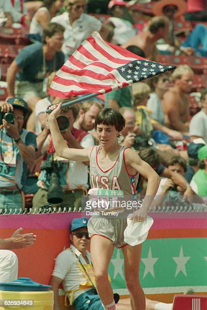 American runner Joan Benoit jogs around the Los Angeles Coliseum track carrying the American flag, after winning the gold medal in the first-ever...