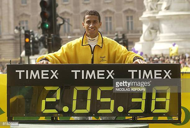 American runner Khalid Khannouchi poses for photographers with the timer after setting a new world record 14 April 2002 during the London marathon