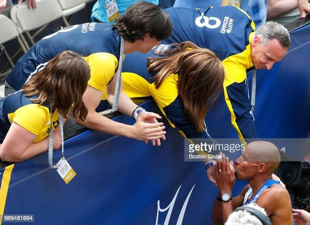 American runner Meb Keflezighi kisses the hand of Denise Richard as other members of the Richard family from left Jane Henry and Bill reach out to...