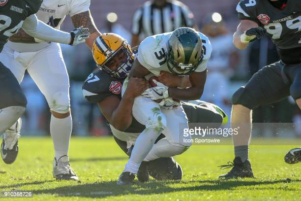 American running back Dalyn Dawkins from Colorado State University runs the ball and Geta tackled by National defensive tackle Frank Herron from LSU...
