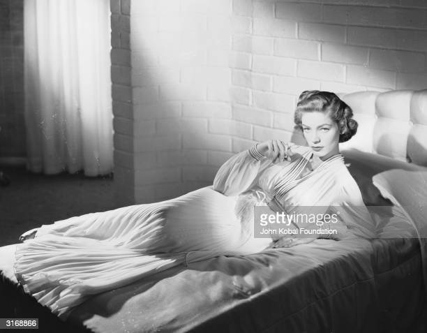 American screen star Lauren Bacall reclines on a bed in a publicity shot for the 1950 movie 'Young Man With A Horn' in which she costars with Kirk...