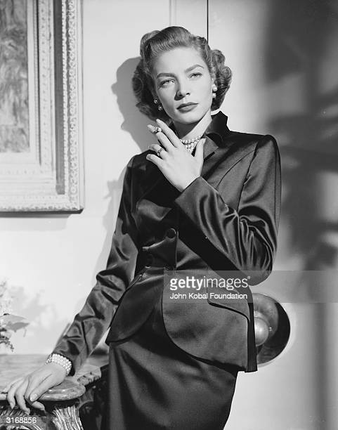 American screen star Lauren Bacall wearing a dark satin suit for her role as Amy North in 'Young Man with a Horn' directed by Michael Curtiz