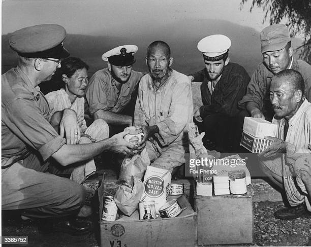 American servicemen giving rations of food and cigarettes to Japanese civilians