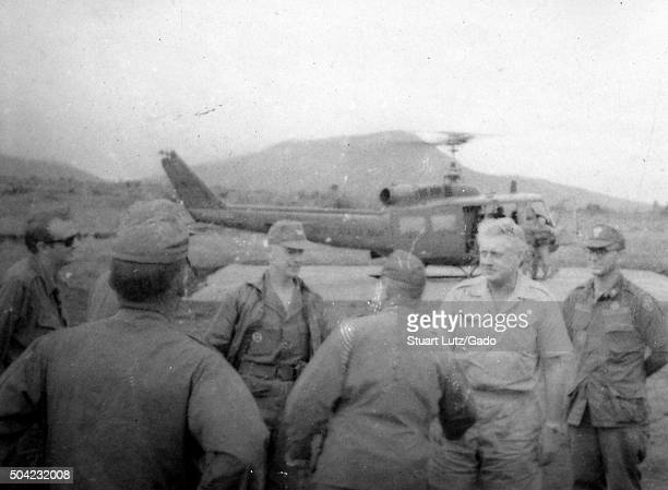 American servicemen in military uniform during the Vietnam War standing in a group a Huey helicopter preparing to take off from a helipad in the...