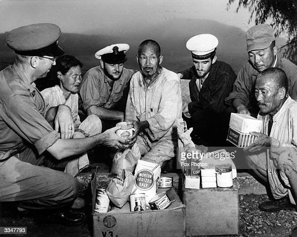 American servicmen giving rations to Japanese civilians during Wirld War II
