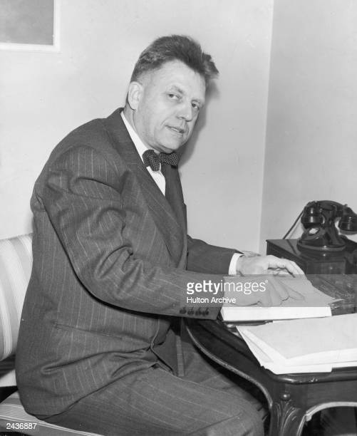 American sexuality researcher Alfred Kinsey looks up while pointing to a passage in a book 1940s