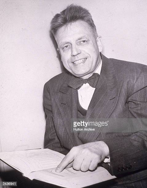 American sexuality researcher Alfred Kinsey smiles while pointing to a passage in a book 1948