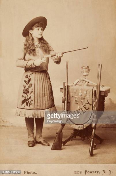 American sharpshooter and exhibition shooter Annie Oakley shows off her guns prior to a trip to England for Queen Victoria's Golden Jubilee 1887...
