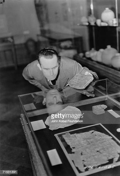 American silent era comedian Harold Lloyd examines a case of hieroglyphic fragments during the filming of Paramount comedy 'Professor Beware' in...