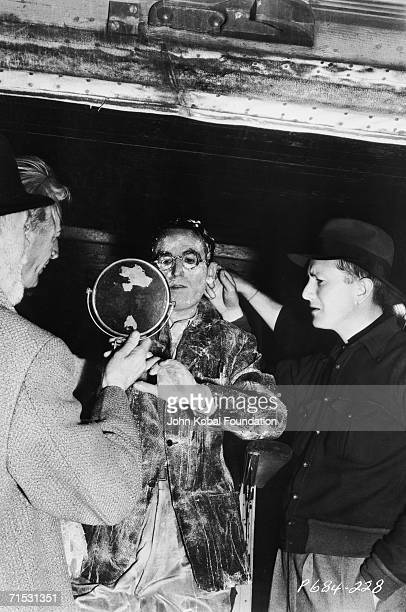 American silent era comedian Harold Lloyd examines his makeup on the set of the Paramount comedy 'Professor Beware' 1938