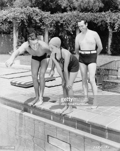 American silent era comedian Harold Lloyd looks on fondly as actor Buster Crabbe gives Lloyd's daughter a swimming lesson at his Beverly Hills estate...