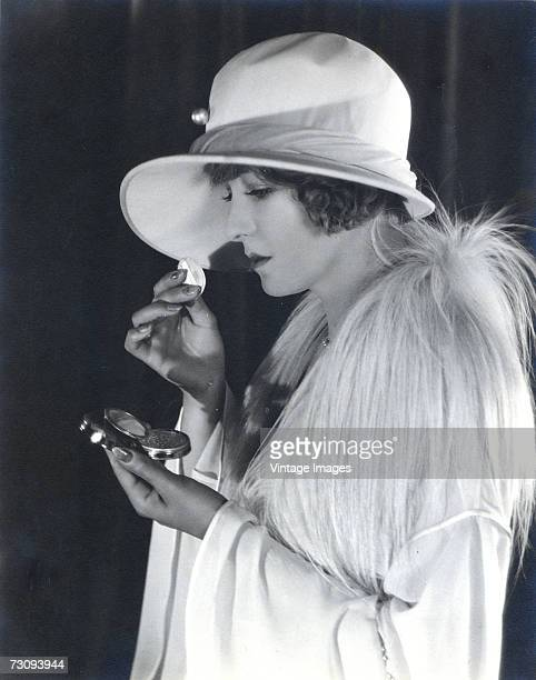 American silent film actress Claire Windsor born Clara Viola Cronk looks in a compact mirror case as she applies makeup to her face and wears a large...