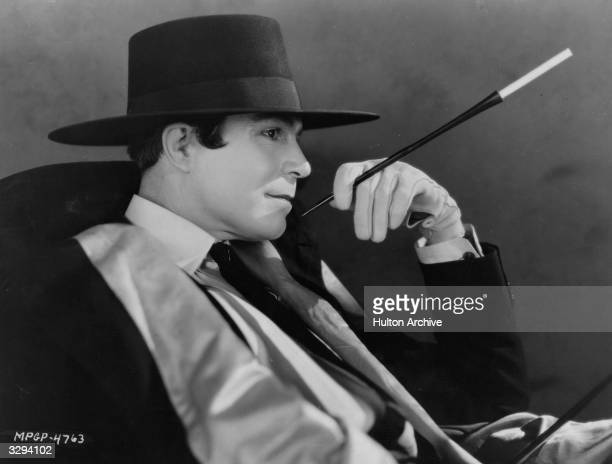 American silent star Harrison Ford poses languidly with a cigarette holder in a scene from the silent comedy 'Proud Flesh' directed by King Vidor for...