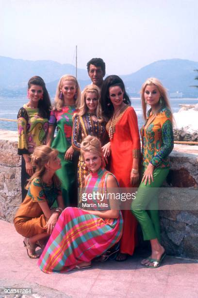 American singer actor and comedian Dean Martin poses with the Slaygirls on the movie set of 'The Ambushers' circa 1967 in Acapulco Mexico