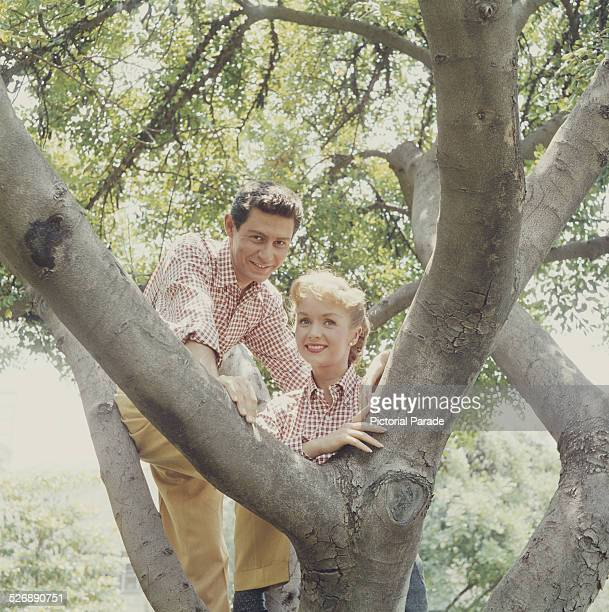 American singer, actor and entertainer Eddie Fisher in a tree with his wife, singer and actress Debbie Reynolds, circa 1955.