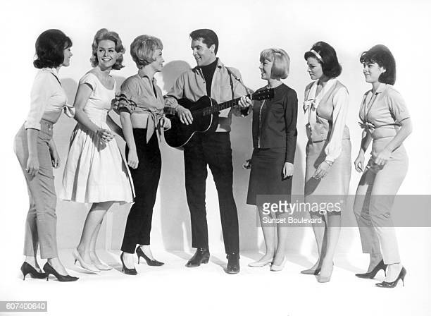 American singer actor and icon Elvis Presley surrounded by actresses Joan Freeman Sue Ane Langdon and Raquel Welch on the set of Roustabout directed...