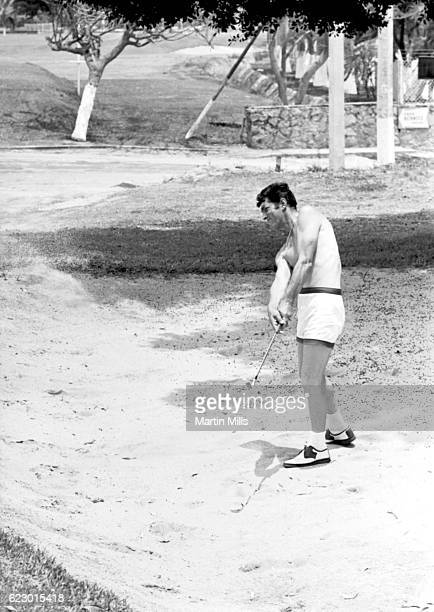American singer actor comedian Dean Martin hits out of a bunker while on location for The Ambushers circa 1967 in Acapulco Mexico