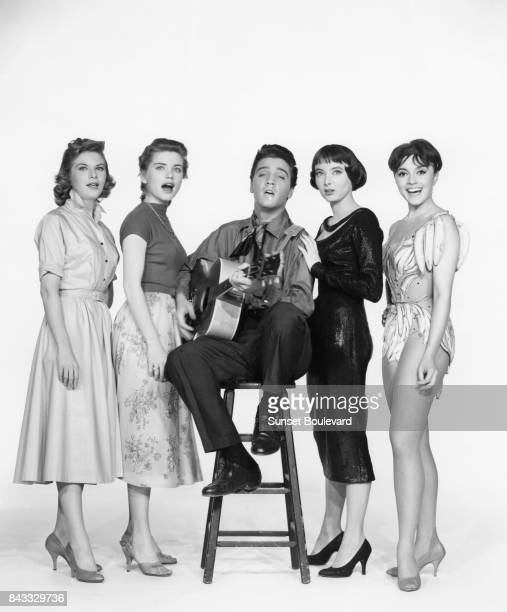 American singer actor Elvis Presley surrounded by actresses Jan Shepard Dolores Hart Carolyn Jones and French actress Liliane Montevecchi on the set...