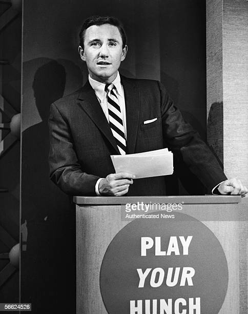 American singer actor talk show host and empresario Merv Griffin holds cards in his hand and leans on the podium as he hosts the premiere episode of...