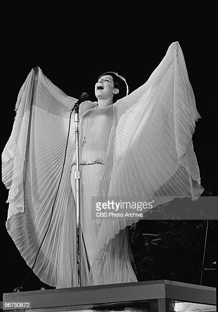 American singer actress and entertainer Barbra Streisand dressed in a flowing gown gestures expansively as she performs at a concert in Central Park...