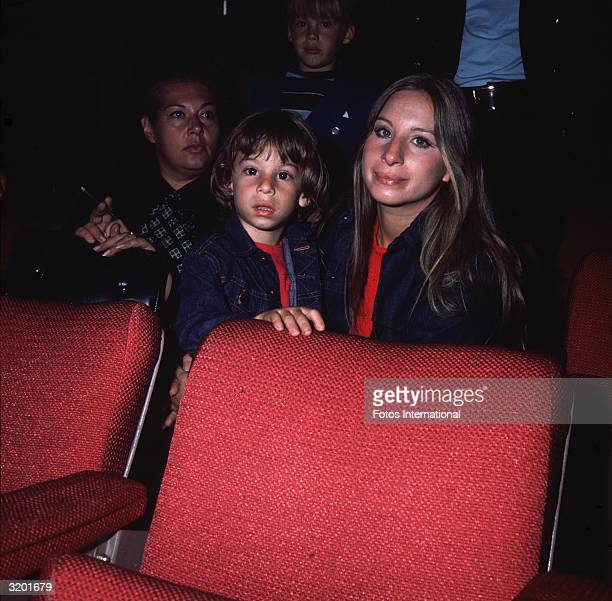 American singer and actor Barbra Streisand seated behind a red movie theater seat with her young son Jason and unidentified theater patrons Jason the...
