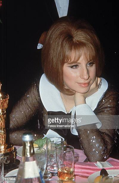 American singer and actor Barbra Streisand sits at a table with her Best Actress Oscar awarded for her role in director William Wyler's film 'Funny...