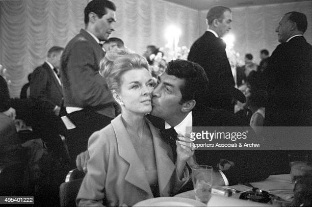 American singer and actor Dean Martin kissing his wife Jeanne Biegger at the premiere of the film My Fair Lady Hollywood 1964