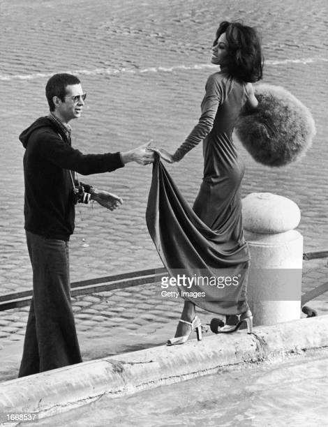 American singer and actor Diana Ross models an evening dress and silver high heels while holding a muff as American actor Anthony Perkins wearing a...