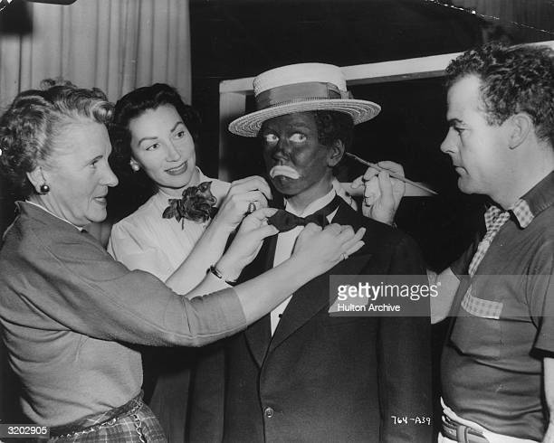 American singer and actor Doris Day frowns while a makeup man touches up the blackface makeup on her ear and wardrobe women fix her tie on the set of...