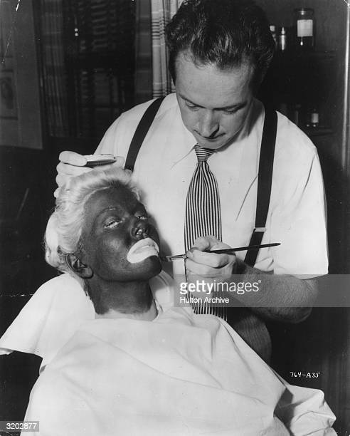 American singer and actor Doris Day leans back in a chair with her chin raised while a makeup man applies black makeup to her face leaving a wide...