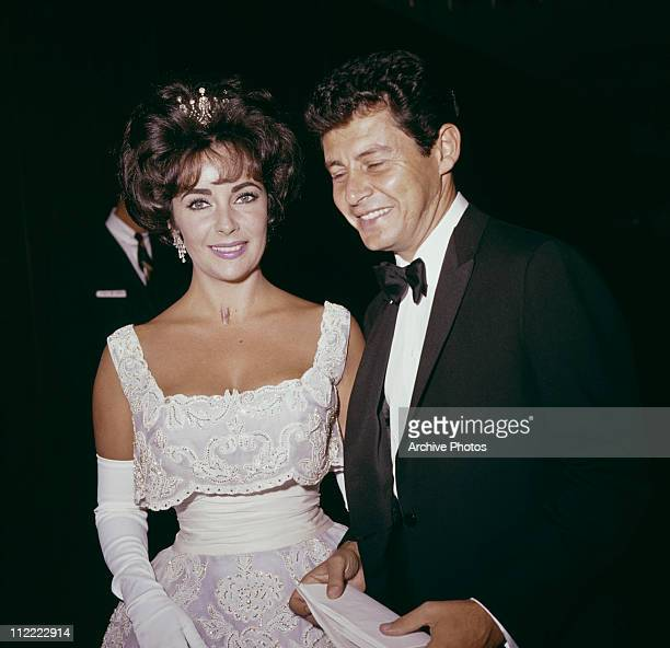 American singer and actor Eddie Fisher and British actor Elizabeth Taylor attend the Academy Awards, Los Angeles, California, circa 1960.