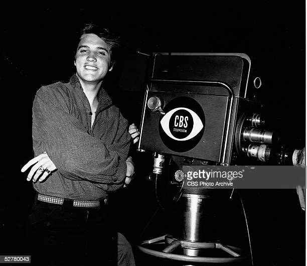 American singer and actor Elvis Aaron Presley stands with his arms crossed by a television camera on the night of his first appearance on 'The Ed...