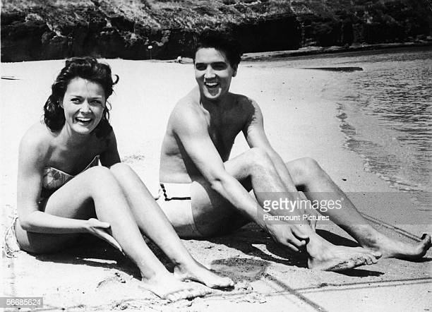 American singer and actor Elvis Aron Presley and American actress Joan Blackman both dressed in swimsuits sit on the beach in a still from the...
