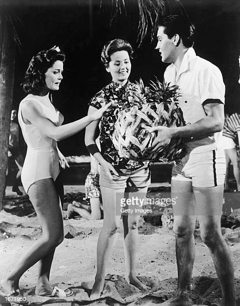 American singer and actor Elvis Presley holds a basket of pineapples in front of American actors Joan Blackman and Pamela Kirk in a still from the...