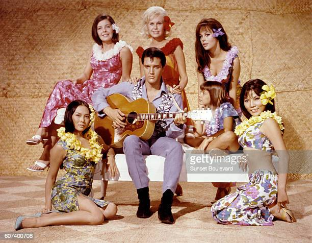 American singer and actor Elvis Presley surrounded by Korean actress Linda Wong American Julie Parrish British Suzanna Leigh American Marianna Hill...