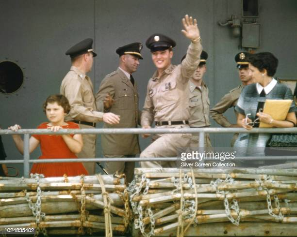 American singer and actor Elvis Presley waves to his fans from the 'USS Randall' at the New York Port of Embarkation's Brooklyn Army Terminal , New...