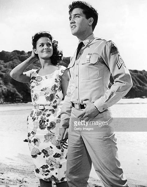 American singer and actor Elvis Presley wearing a military uniform holds hands with American actor Joan Blackman on the beach in a still from the...