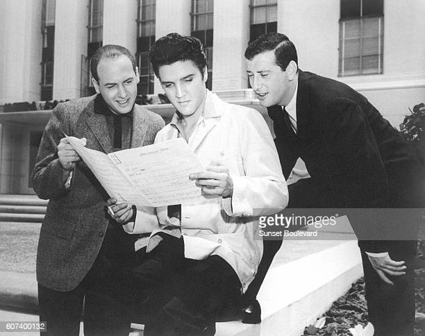 American singer and actor Elvis Presley with songwriters Mike Stoller and Jerry Leiber looking over the sheet music on the set of Jailhouse Rock...