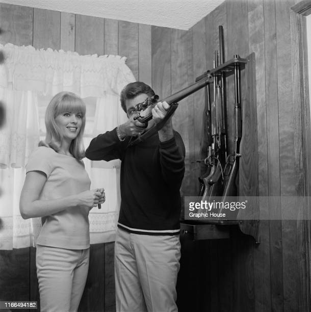American singer and actor Fabian Forte at home with his wife Kathleen Regan and his rifle collection circa 1968