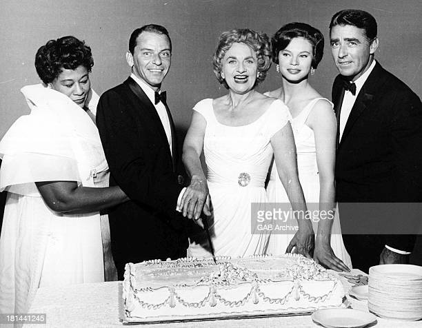 American singer and actor Frank Sinatra and English actress Hermione Gingold cutting their joint birthday cake December 1959 Left to right singer...