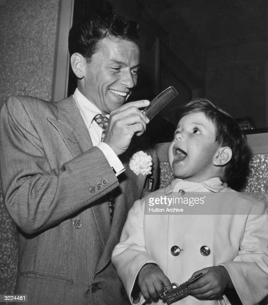 American singer and actor Frank Sinatra combs the hair of his son Frank Jr on the set of director Richard Whorf's film 'It Happened in Brooklyn' in...