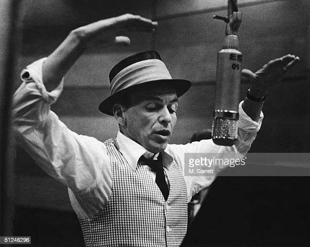 American singer and actor Frank Sinatra gestures with his hands while singing into a microphone during a recording session in a studio at Capitol...