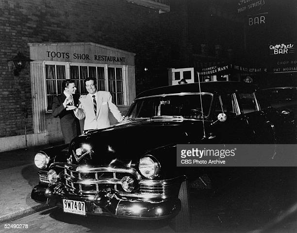American singer and actor Frank Sinatra hands over the keys to a Cadillac to American actor and comedian Jackie Gleason in front of Toots Shor's...