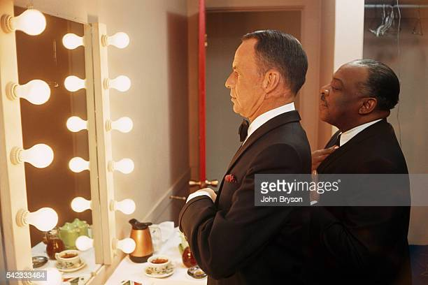 American singer and actor Frank Sinatra in his dressing room with composer pianist and bandleader Count Basie