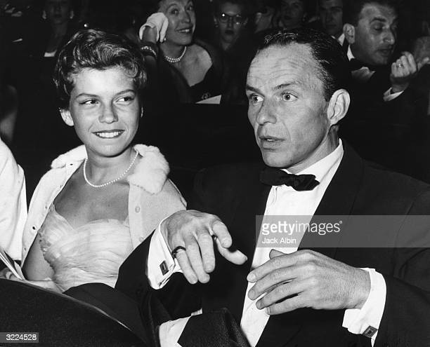 American singer and actor Frank Sinatra sits next to his daughter Nancy Sinatra at the premiere of director Stanley Kramer's film 'Not As a Stranger'...